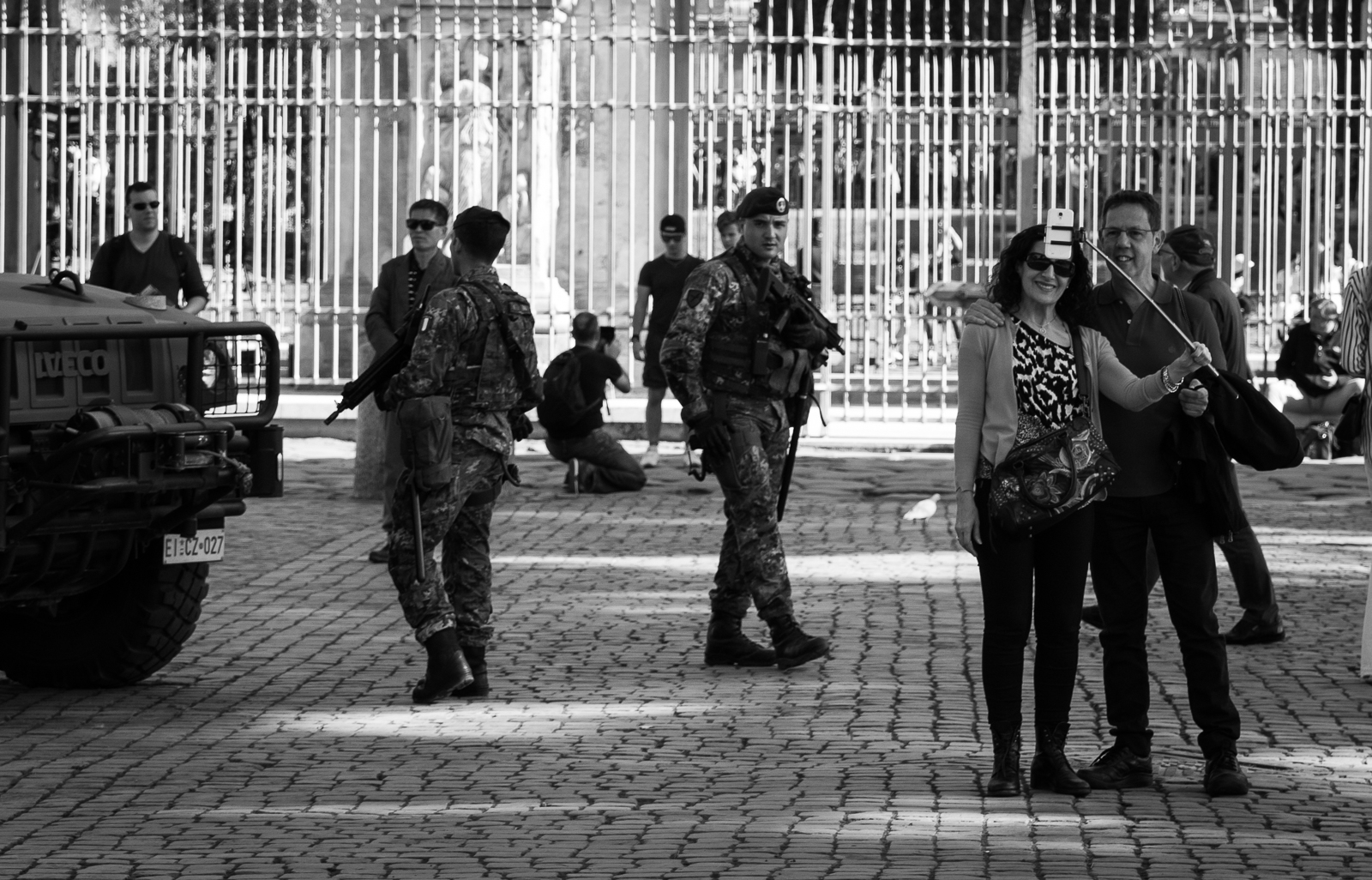 On the one hand you have the smiling people but very close are the heavily armed soldiers.
